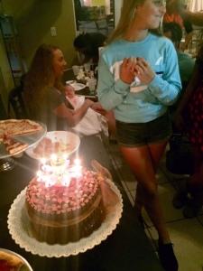Amya standing by cake